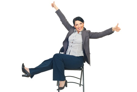 Successful business woman siting on chair raising legs and arms and giving thumbs up isolated on white background photo