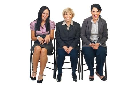 laughing out loud: Tres mujeres de negocios, sentados en sillas vista algo y riendo a carcajadas juntos aislaron sobre fondo blanco