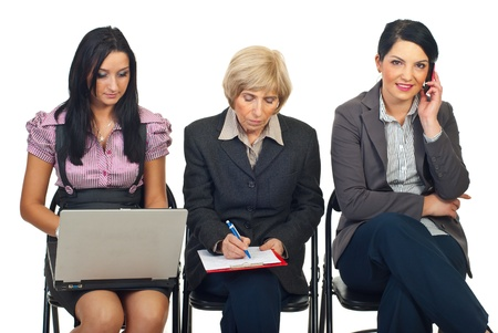 Three businesswomen at conference or course do different works :one talking by phone mobile,senior woman writing in clipboard,takking notes and last woman typing on laptop Stock Photo - 8436001
