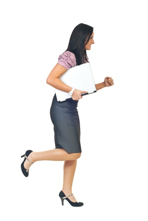 haste: Young executive woman in hurry running and holding a silver laptop isolated on white background Stock Photo