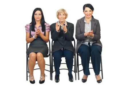 Three business women sitting on chairs in a row and clapping their hands isolated on white background Stock Photo - 8436022