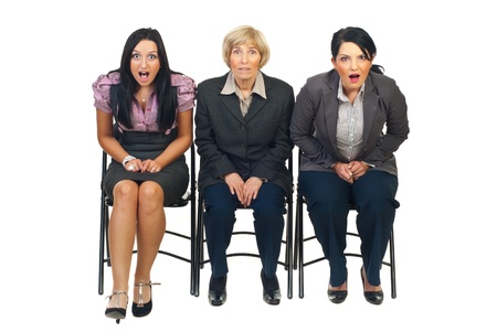 is astonished: Shocked group of businesswomen sittingon chair at conference isolated on white background