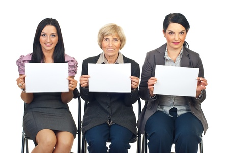 Group of three business women sitting on chairs in a line showing blank pages isolated on white background Stock Photo - 8436026
