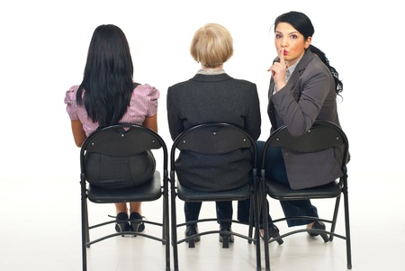 Three business women sitting on chairs viewing a presentation and one of them return her head to  tell you to be quiet Stock Photo - 8436027