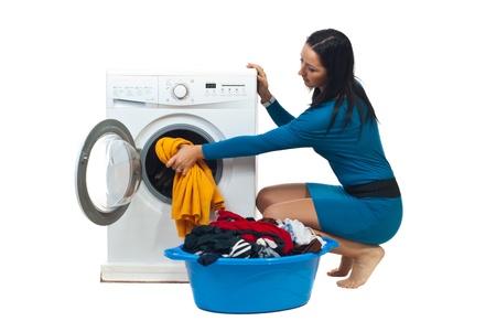 lavadora de ropa: Joven ama de casa en vestido azul cargar la lavadora aislado sobre fondo blanco