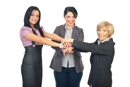 United team of business women standing with hands on top each other and smiling isolated on white background Stock Photo - 8493148