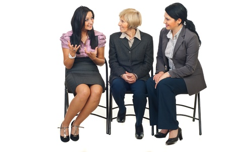 woman speaking: Three business women having a happy discussion at conference and sitting on chairs isolated on white background