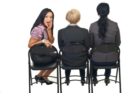 Rear view of three business woman in a row watching  a presentation and one of them returns her head with amazed face isolated on white background photo
