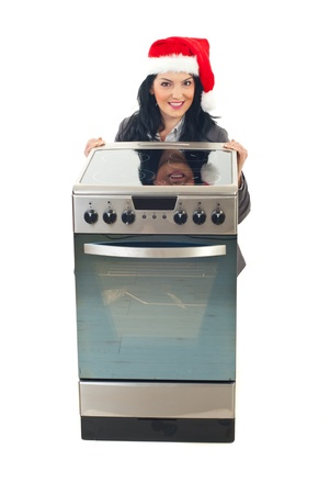 Woman with Santa hat making a Christmas promotion at electrical stove isolated on white background photo