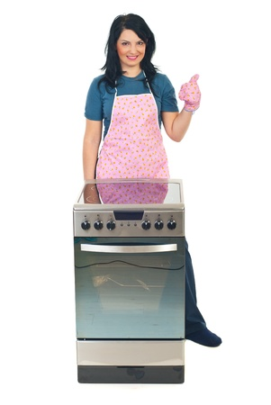 Successful cook woman with new electrical stove giving thumb up in her glove isoalted on white background photo