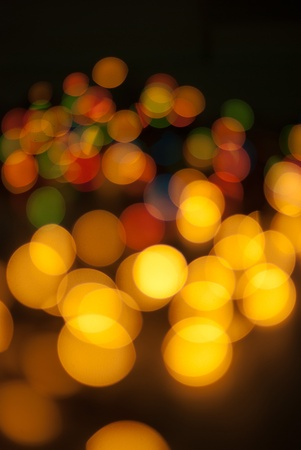 Christmas tree lights bokeh with yellow lights in front of image and colorful lights in background photo