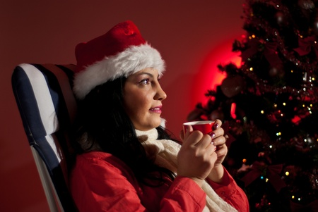 Beautiful woman with Santa hat drinking hot tea and sitting on chair near Christmas tree with lights in night photo