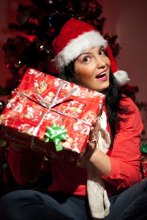 Excited woman in Christmas night sitting near tree and lifting her Christmas gift to listen whats inside photo