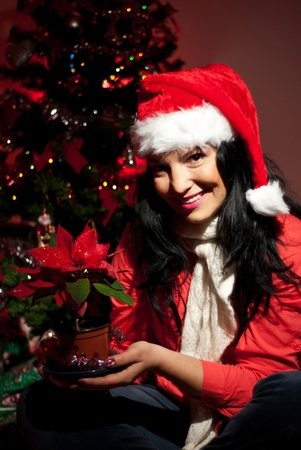 Happy woman with Santa hat sitting on floor near tree with lights and holding a pot with red poinsettia in Christmas night photo