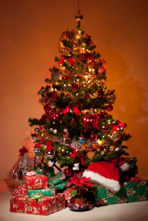 Beautiful Christmas tree with gifts ,flower and lights glowing in night  photo