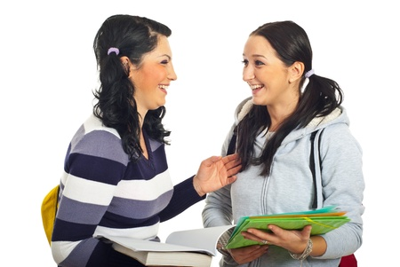 teenage girls: Two students girls standing face to face  having an conversation and laughing together isolated on white background