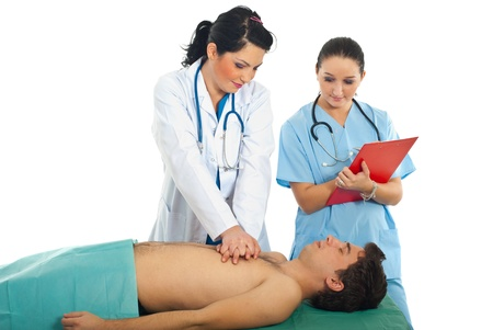 compressions: Doctor training a student to do cardiopulmonary resuscitation on male patient Stock Photo