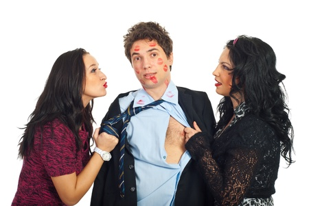 cheating: Two women  pulling the clothes of a man to kiss him and he is amazed and tired by so many kisses
