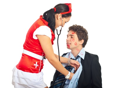 Sexy nurse examine a  lover male patient in business suit isolated on white background photo