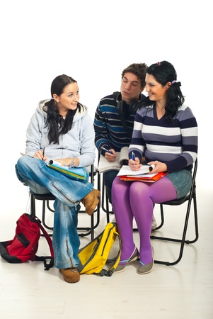 discuss: Students having a conversation and sitting on chairs in a classroom Stock Photo