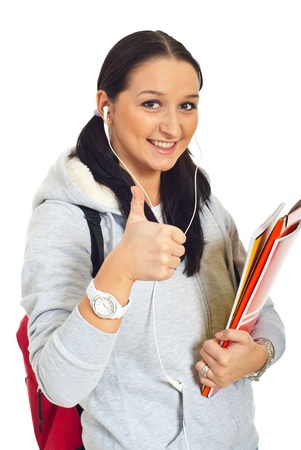 Smiling student woman giving thumb up and holding notebooks isolated on white background photo
