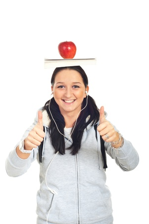 Successful student female holding book and apple on her head and giving thumbs up isolated on white background photo