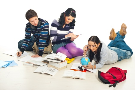 Three students sitting on wooden floor having a conversation and working together at homework  photo
