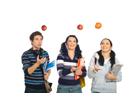 Three cheerful students throw up apples and having fun isolated on white background photo