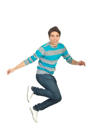 Casual man in blue pullover and jeans jumping and smiling isolated on white background