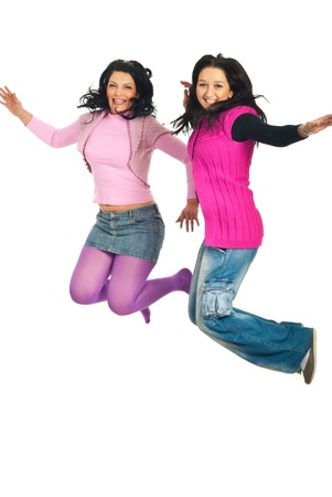 Two young women friends jumping together and laughing isolated on white background photo