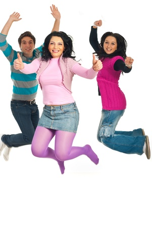 Three cheerful friends jumping and one  woman giving thumbs up isolated on white background photo