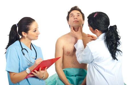 Physician woman eamine neck male patient checking for thyroid problem or sore throat and a nurse taking notes in clipboard Stock Photo