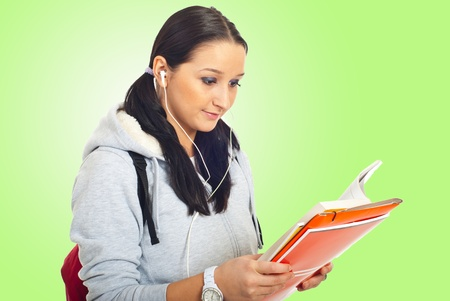 Student girl reading and listening music in earphones over green background photo