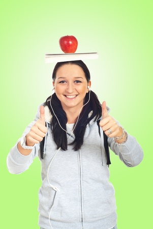 Student girl giving thumbs and holding book and apple on her head over green background photo