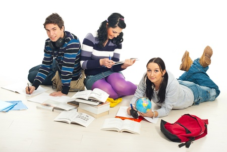 Three students make their homework together  and sitting on wooden floor in a home photo