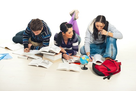 Three student lying down on wooden floor and make their homework photo