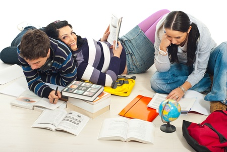 Three friends studying together home and sitting on wooden floor photo