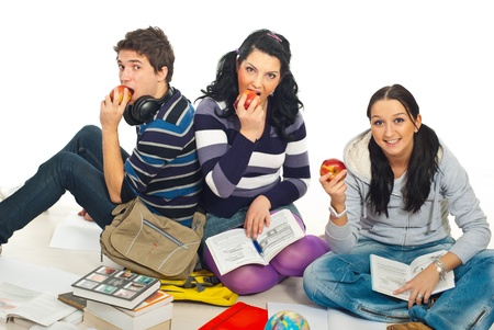 Happy healthy students eating  apples and sitting on wooden floor and studying together photo
