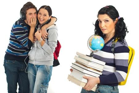 laughing out loud: Dos estudiantes susurro cuenta secretos y riendo en voz alta sobre un colega femenino con sorprendieron a cara triste que llevando la pila de libros pesados