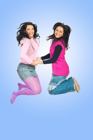 Happy two women jumping and holding their hands over blue background photo