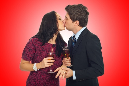 Kissing couple on Valentines  day ,man holding her hand with wedding ring and toasting with champagne on red background photo