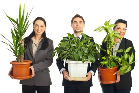 plant pot: Happy business people holding big vases with plants and standing in a row  isolated on white background Stock Photo