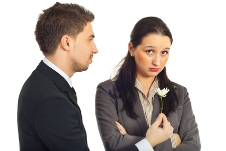 sorry: Business man offering a little flower to his sad colleague woman with the message:Fogive me that i was wrong! isolated on white background