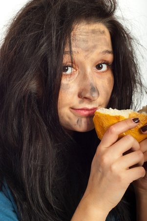 smutty: Close up of hungry beggar woman holding piece of bread and preparing to eat Stock Photo