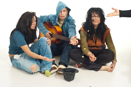 Three beggars singing with guitar and receive coins from someone in their hat photo
