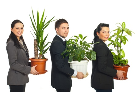 flower show: Line of three business people standing in profile and holding big vases with plants isaolated on white background Stock Photo