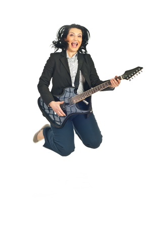 Cheerful formal woman playing guitar ,jumping and shouting isolated on white background photo