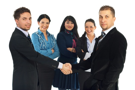 hand wear: Two business men give handshake in front of camera  and other three business women smiling in the background