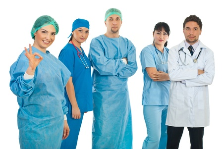 Surgeon woman giving okay sign hand gesture and her team standing with arms folded in background photo