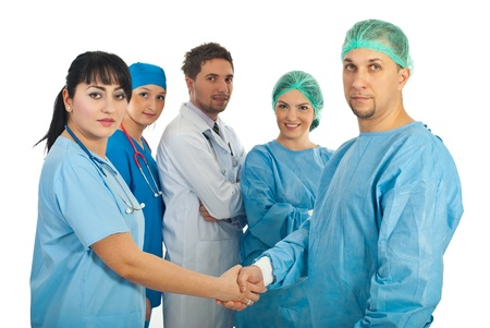 Physician woman and surgeon man handshake and their team of doctors standing with hands crossed in the middle of them isolated on white background photo